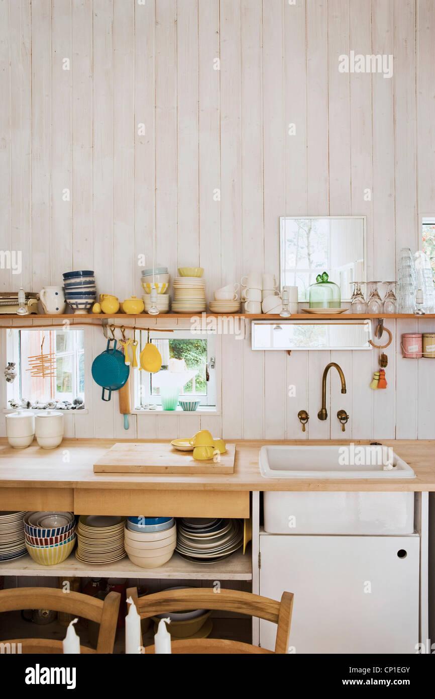 Kitchenware on shelf above sink set in wooden worktop in country ...
