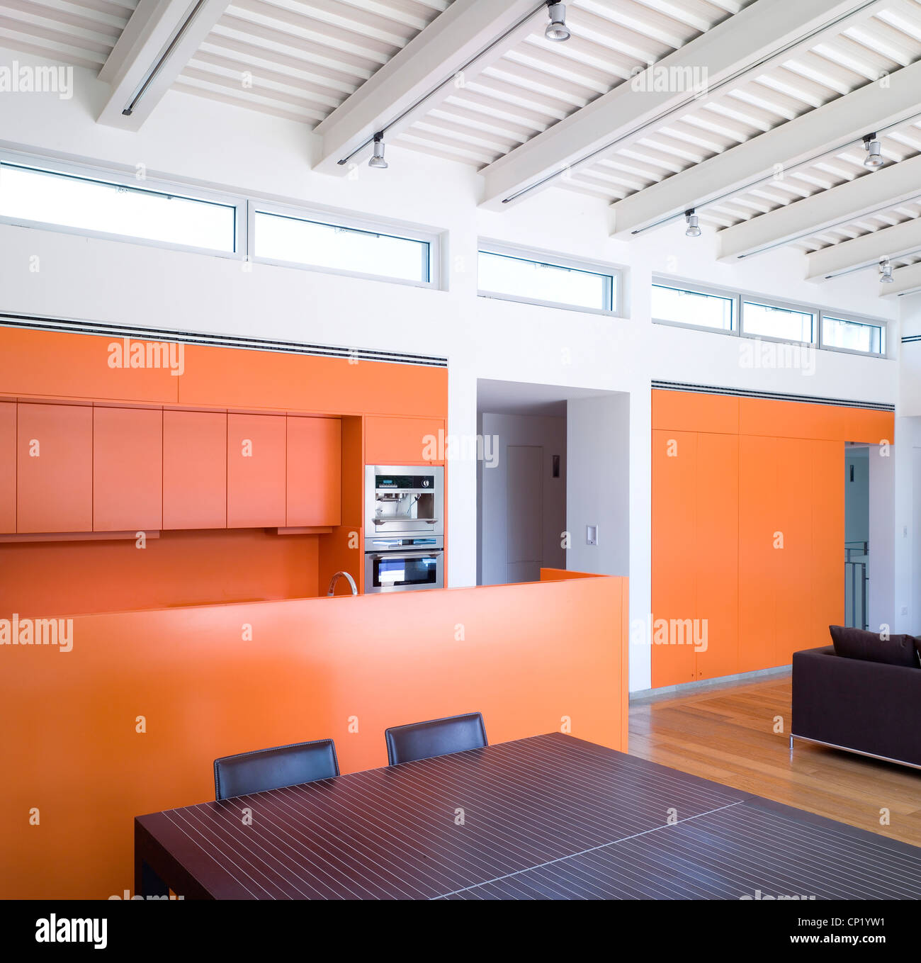 Open Plan Kitchen Dining Living Room With Orange Walls And Line Of Clerestory Windows