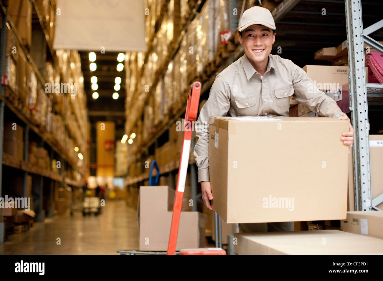 Male chinese warehouse worker carrying boxes stock photo royalty male chinese warehouse worker carrying boxes sciox Choice Image