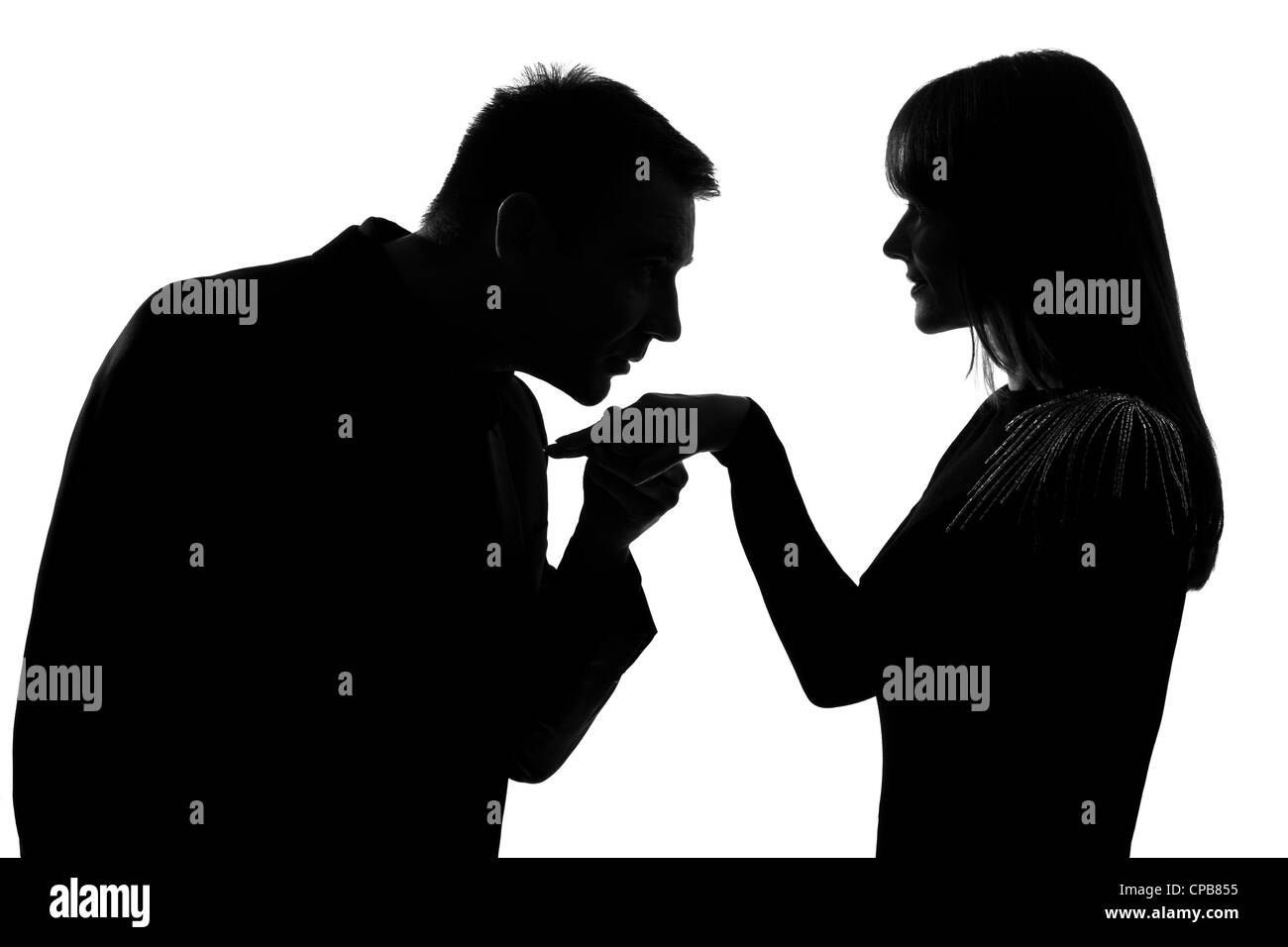 one caucasian man kissing hand woman in studio silhouette isolated on white background