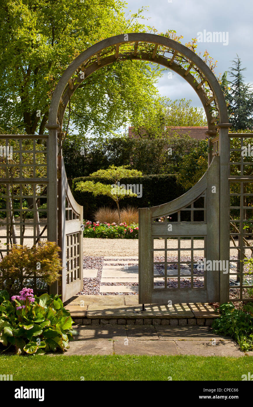 Garden Feature Arch With Gates Leading Into Stone And Pebble Area