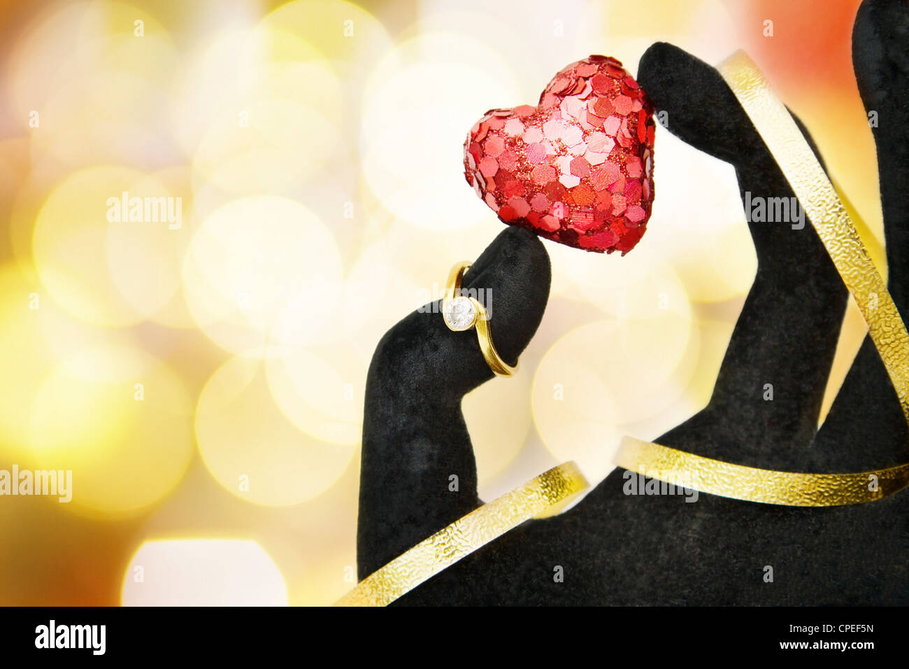 Marry me hand giving diamond engagement ring and sparkling red hand giving diamond engagement ring and sparkling red heart as a symbol of love over defocused lights with room for biocorpaavc