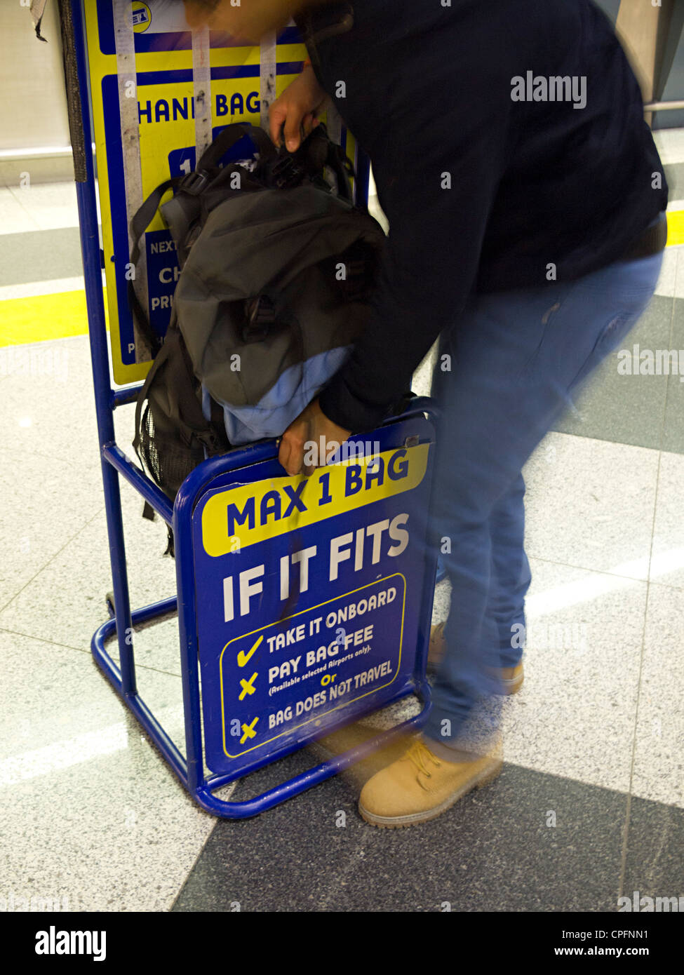 Person Trying To Fit Backpack In Ryanair Size Limit Stock