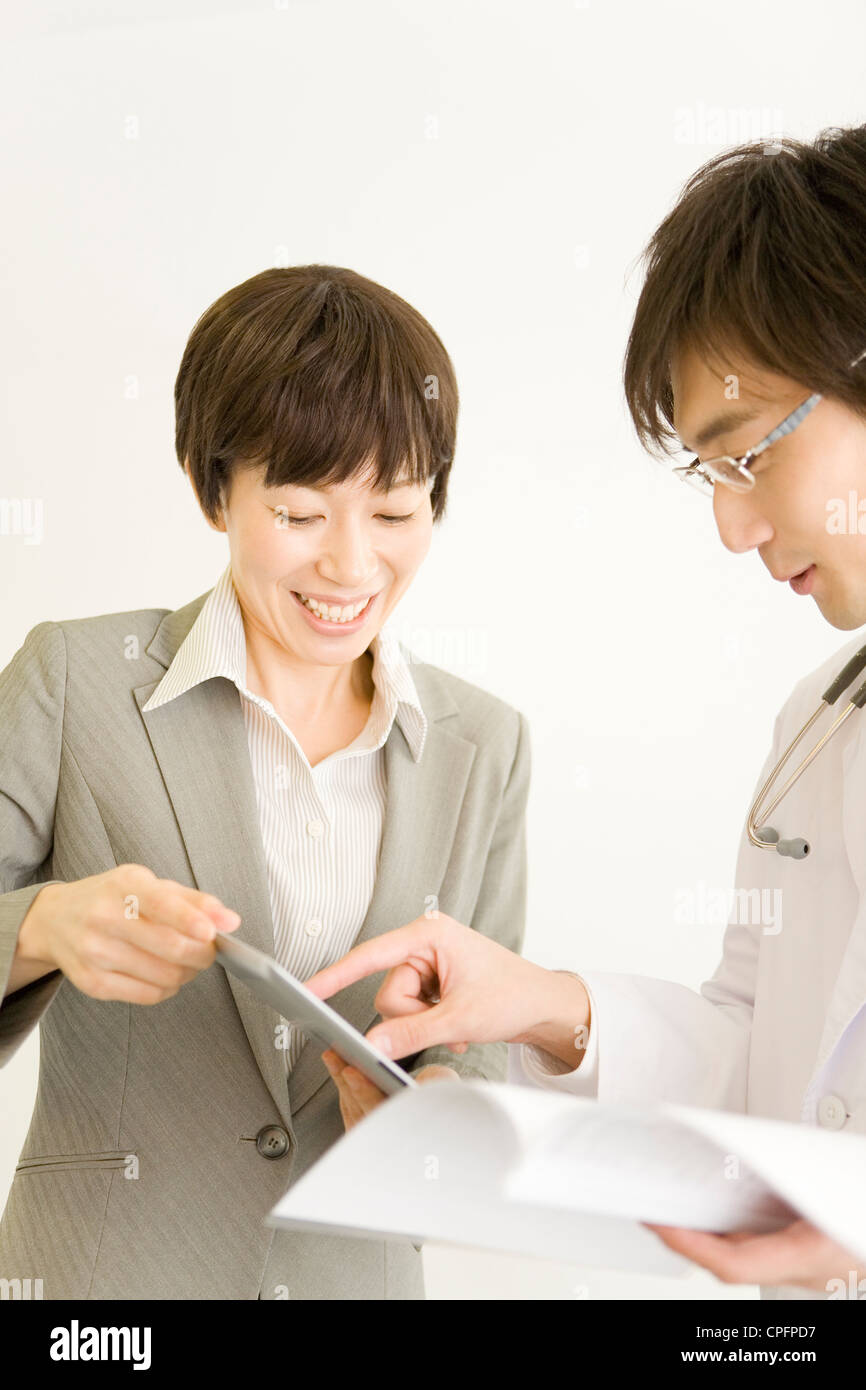 doctor and pharmaceutical s representative looking tablet doctor and pharmaceutical s representative looking tablet computer