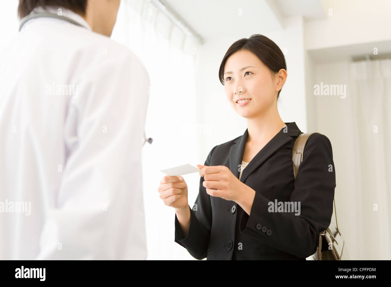 pharmaceutical s representative presenting card to doctor pharmaceutical s representative presenting card to doctor