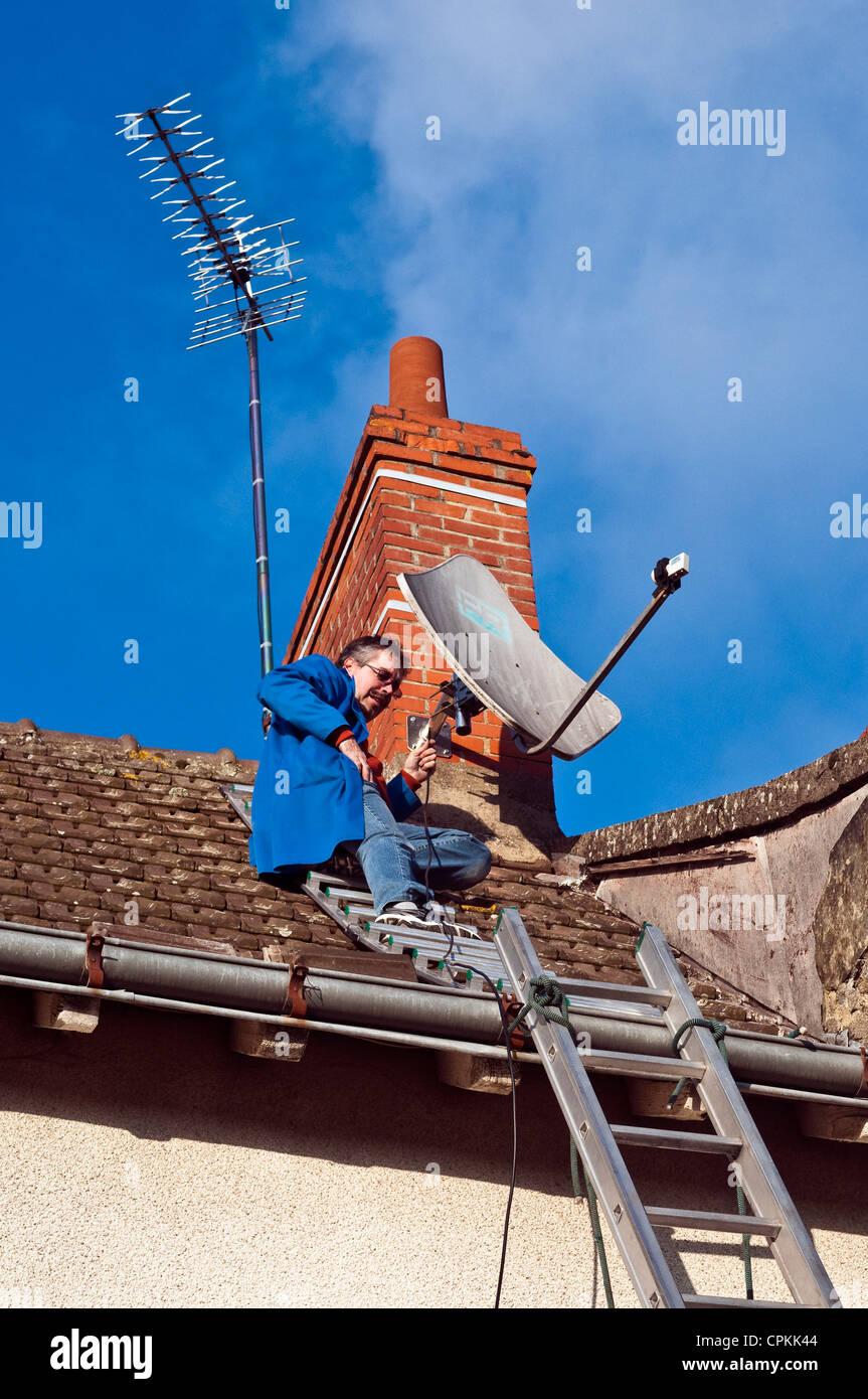 Television technician fixing satellite dish on house chimney – Satellite Dish Technician