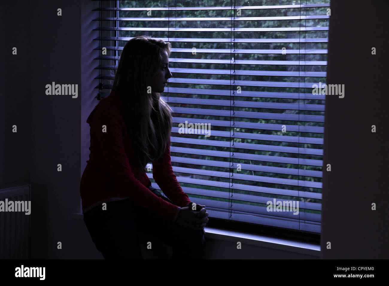 Dark room with light through window - Young Female Sitting Alone In A Dark Room Looking Out Through A Window Blind
