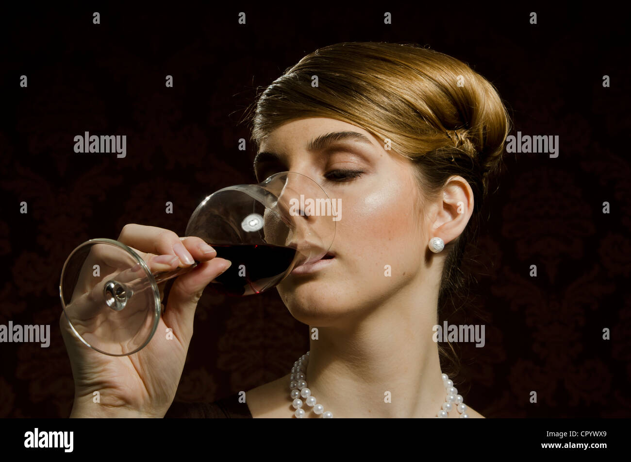 Stock Photo  Young Woman Wearing A Pearl Necklace And Pearl Earrings,  Drinking Red Wine In A Wine Glass