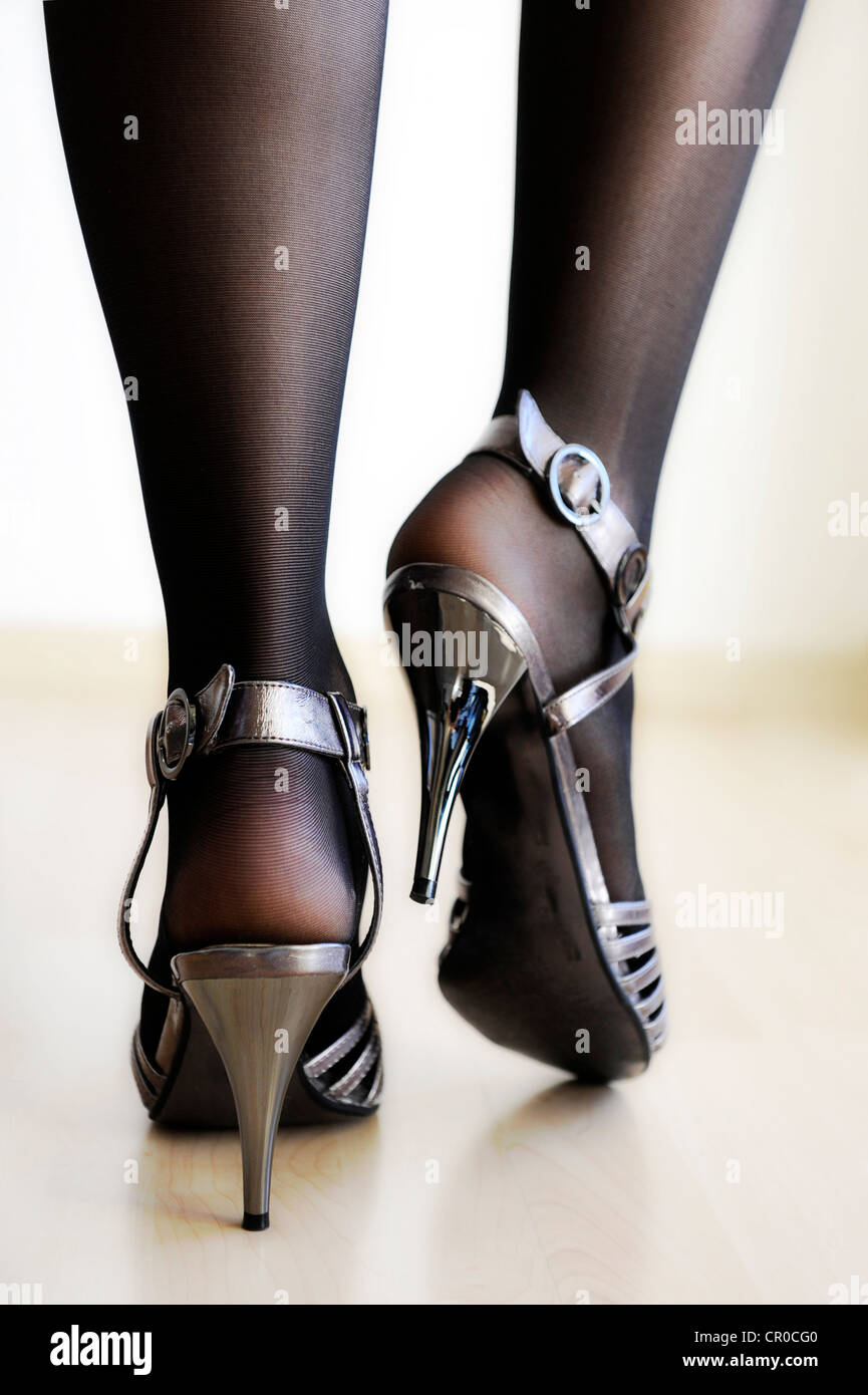 Woman's Legs Wearing Black Stockings And Silver High Heels Stock ...