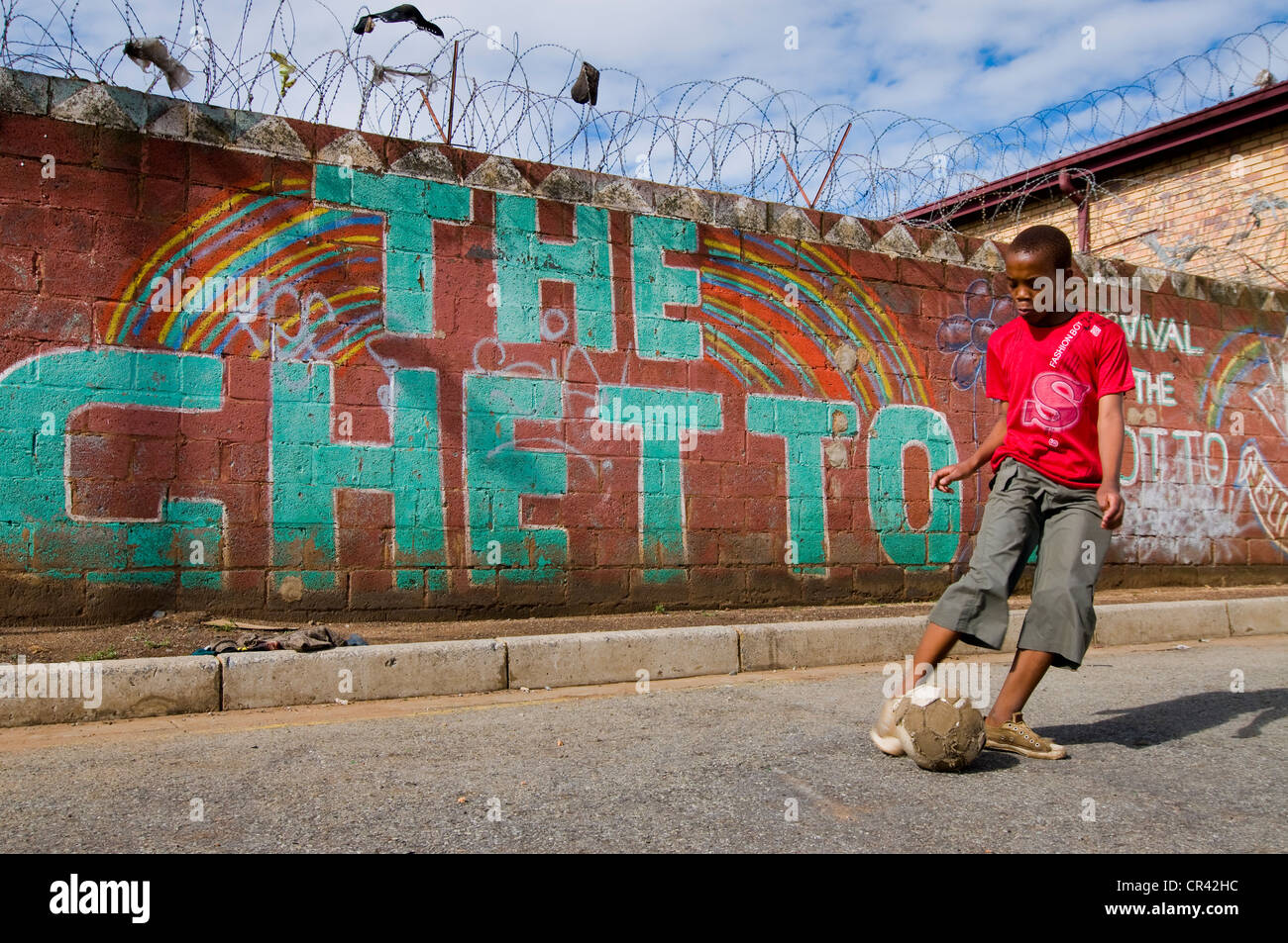 boy playing football in front of wall with the word