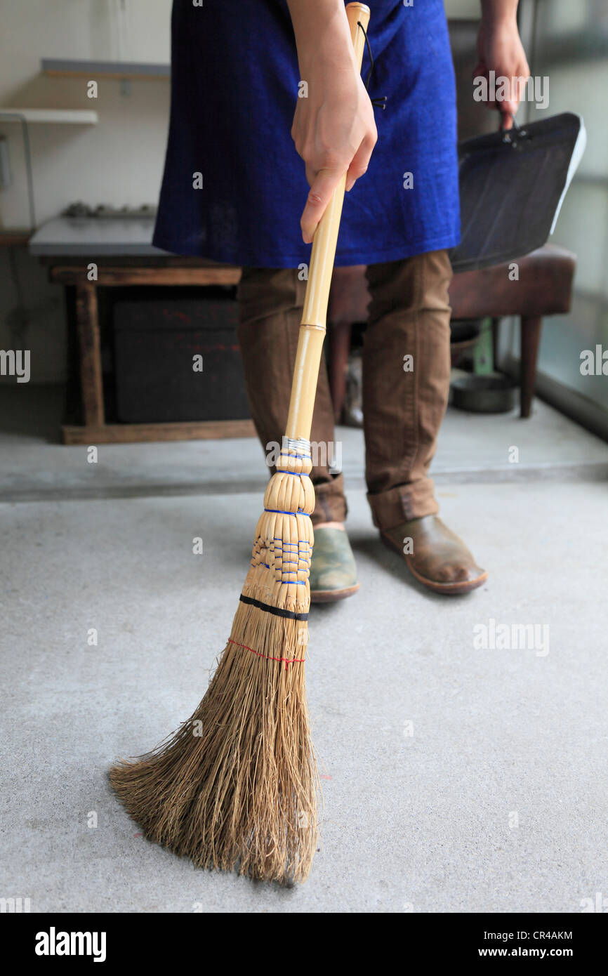 Young Woman Sweeping Room with Broom