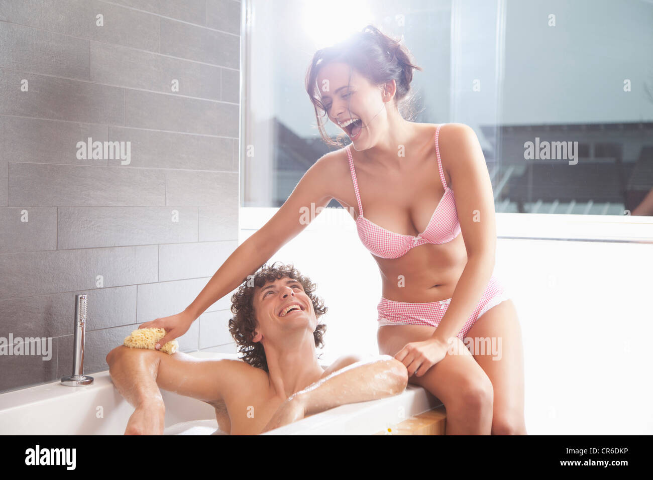 Germany  Bavaria  Young woman bathing man in bathroom. Germany  Bavaria  Young woman bathing man in bathroom Stock Photo