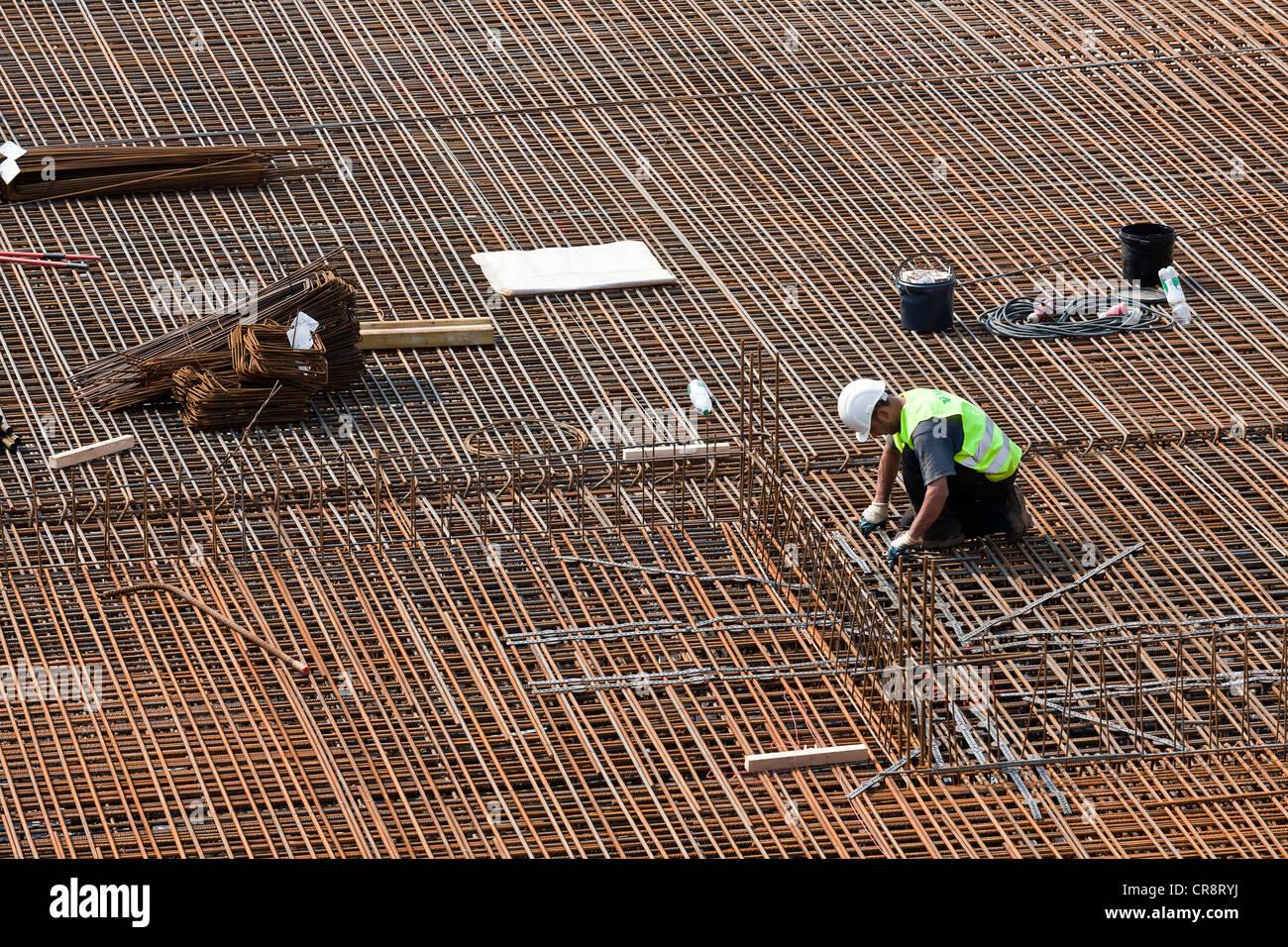 construction worker installing steel rebar beams for reinforced concrete building site rebar worker