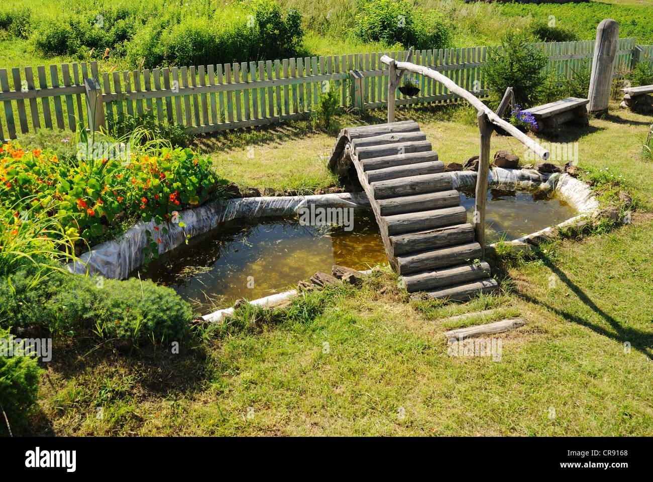 Small garden pond with wooden bridge in summer stock photo for Garden pond bridge