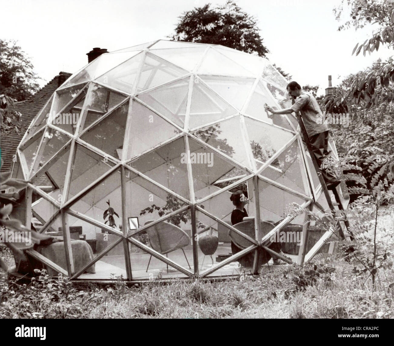 Dome House Futuristic: Husband Cleaning Windows On Geodesic Dome House Stock