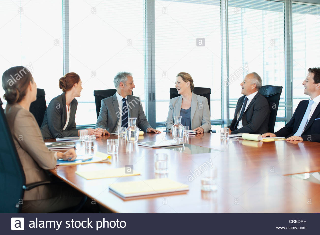 Smiling business people meeting at table in conference ...