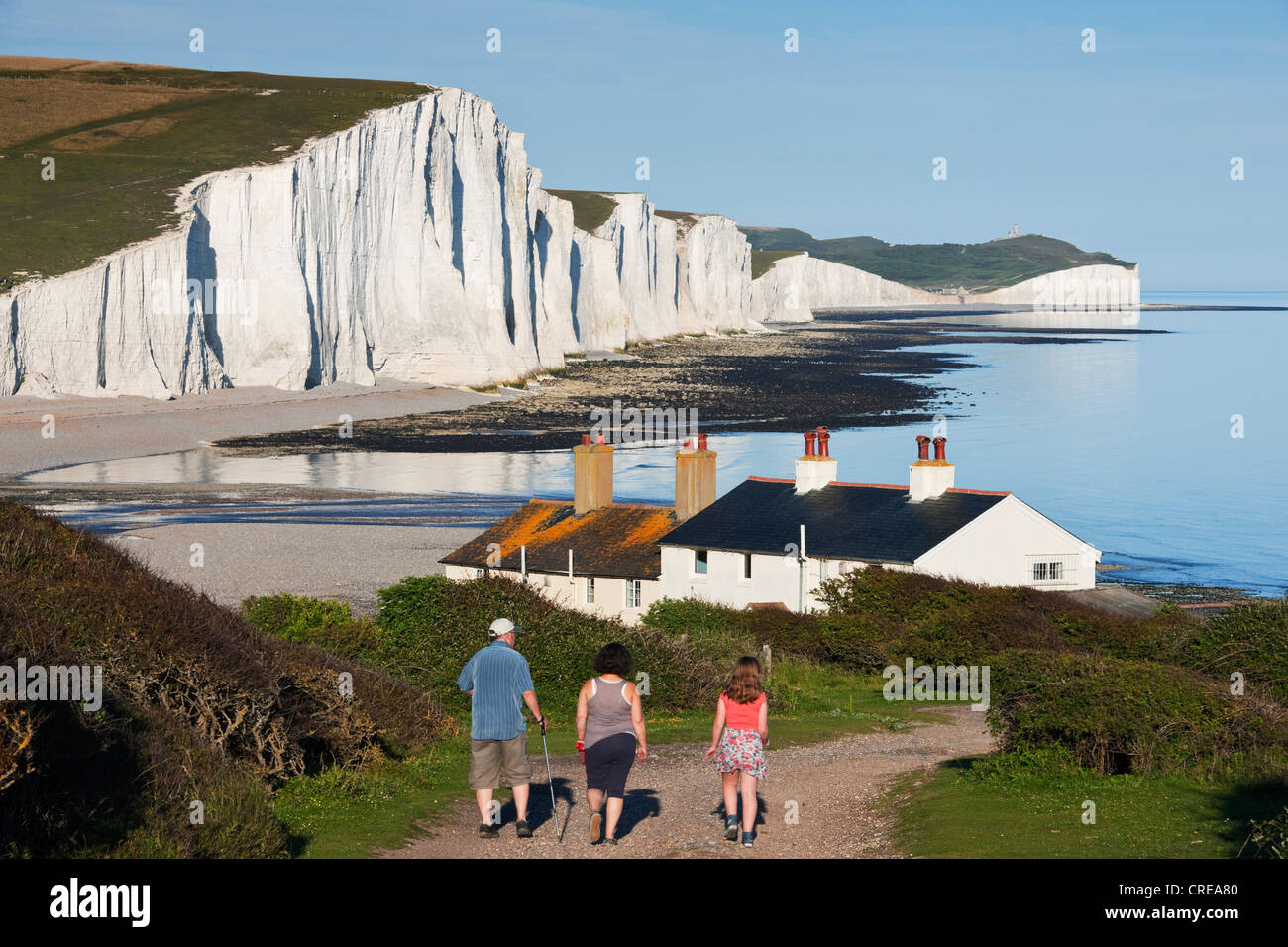 a family walk towards seven sisters by the cuckmere estuary with