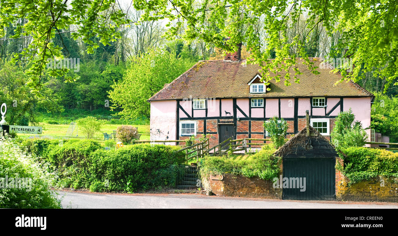 English Country Cottage Which Used To Be A Village Pub Painted Pink With Finger Post For Petersfield On Sussex Hampshire Border