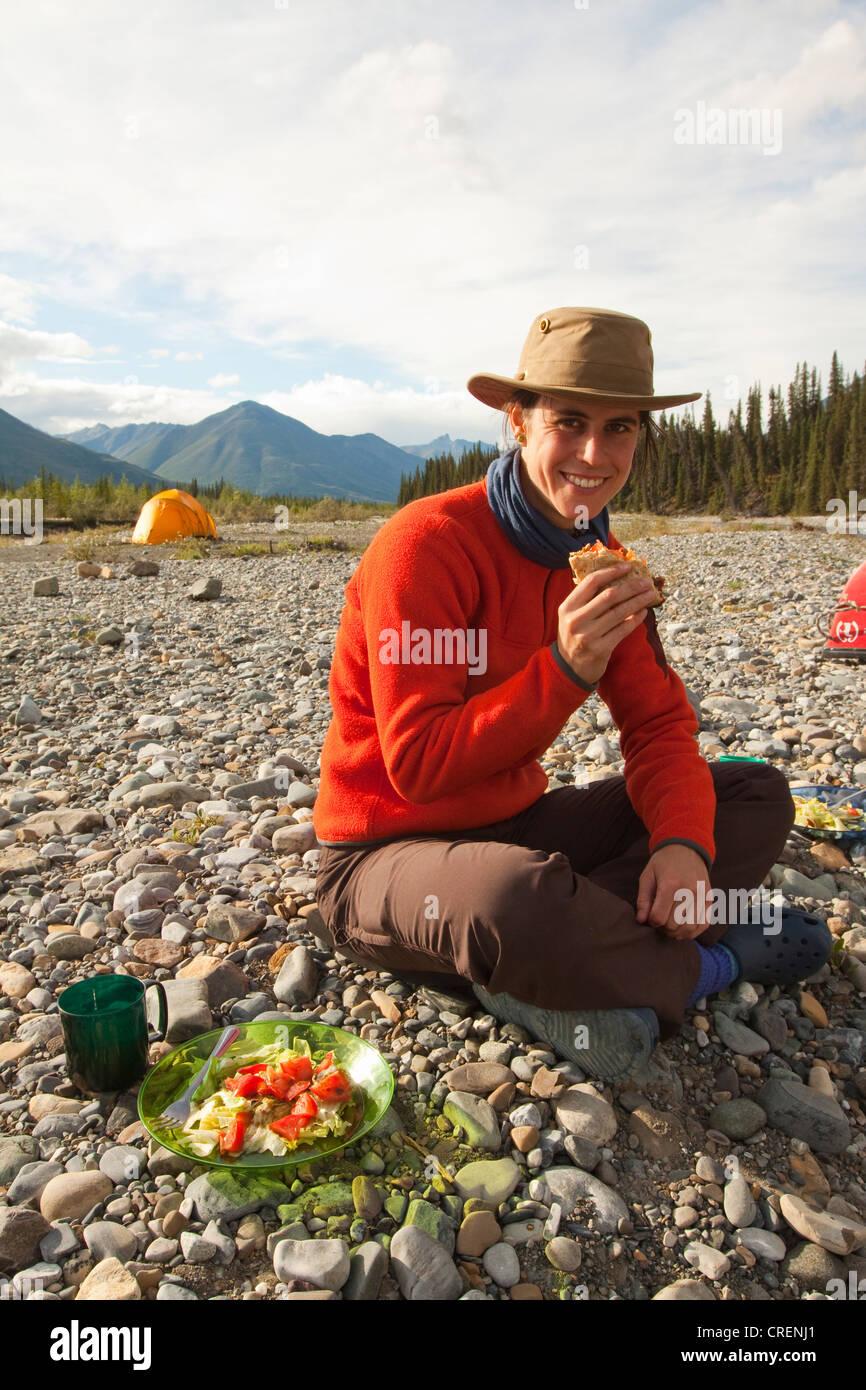 Young woman enjoying a hamburger tent behind c&ing Wind River Yukon Territory Canada & Young woman enjoying a hamburger tent behind camping Wind River ...