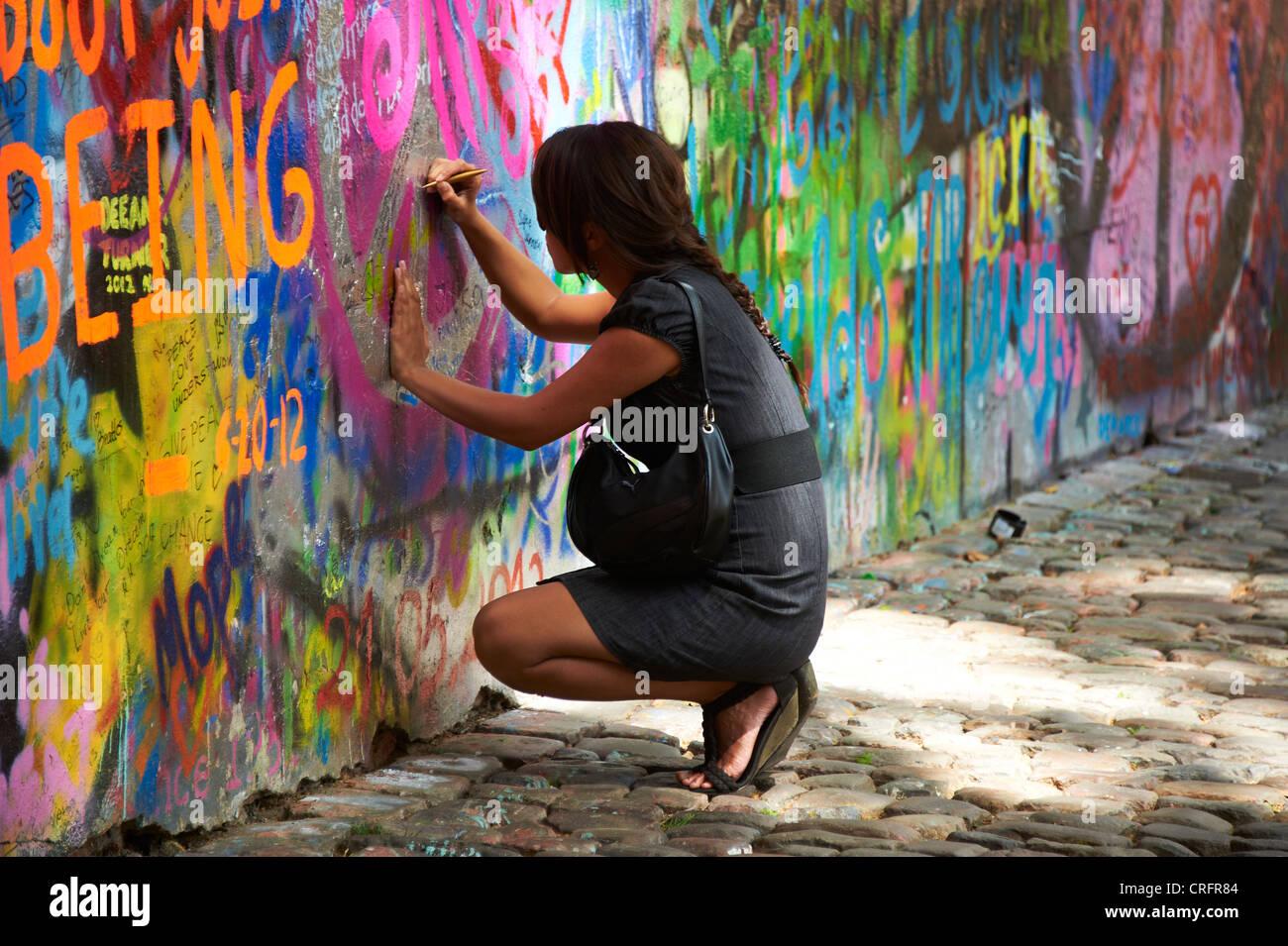 Graffiti wall writing - Stock Photo The John Lennon Graffiti Wall In Prague Czech Republic Tourist Woman Painting And Writing Testament