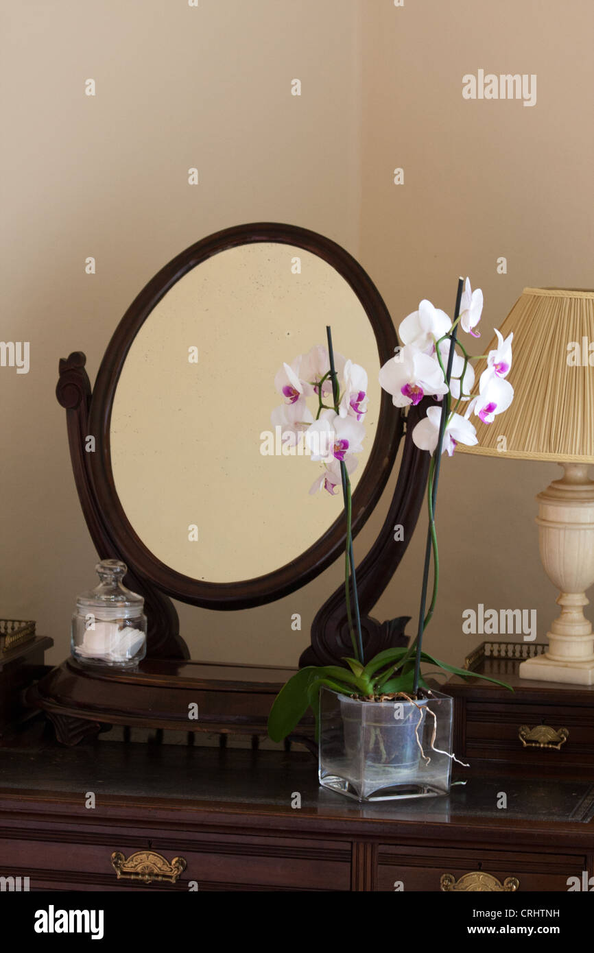 a traditional hotel interior dressing table with mirror and lamp offset by fresh flowers - Traditional Hotel Interior