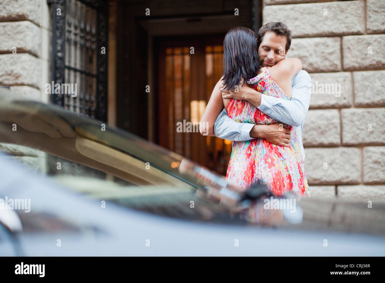 Couple hugging by car on city street. Couple Hugging By Car On City Street Stock Photo  Royalty Free