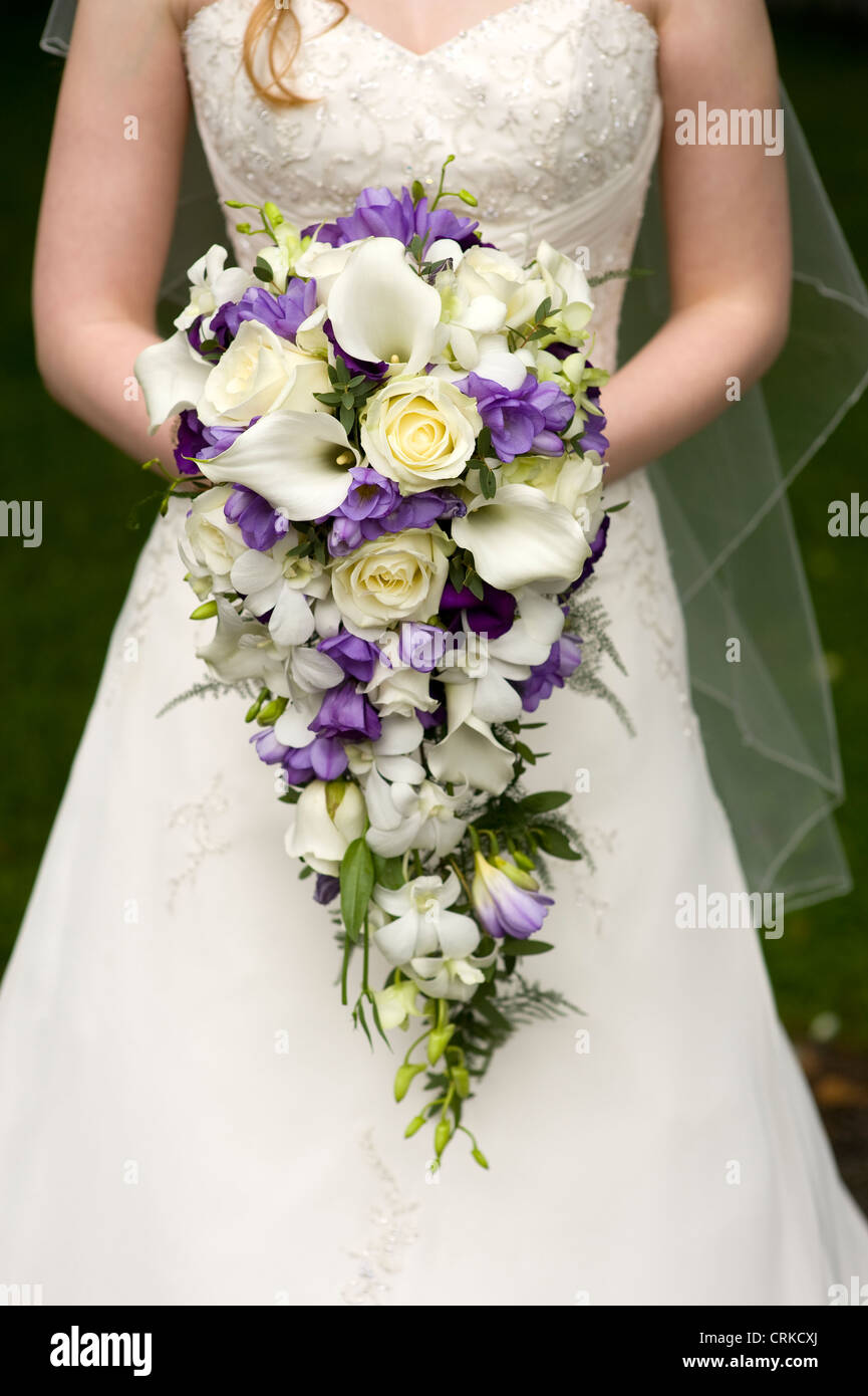 Bride holding a large teardrop wedding bouquet with purple flowers stock photo bride holding a large teardrop wedding bouquet with purple flowers including rose roses lily lilies freesia dhlflorist Image collections
