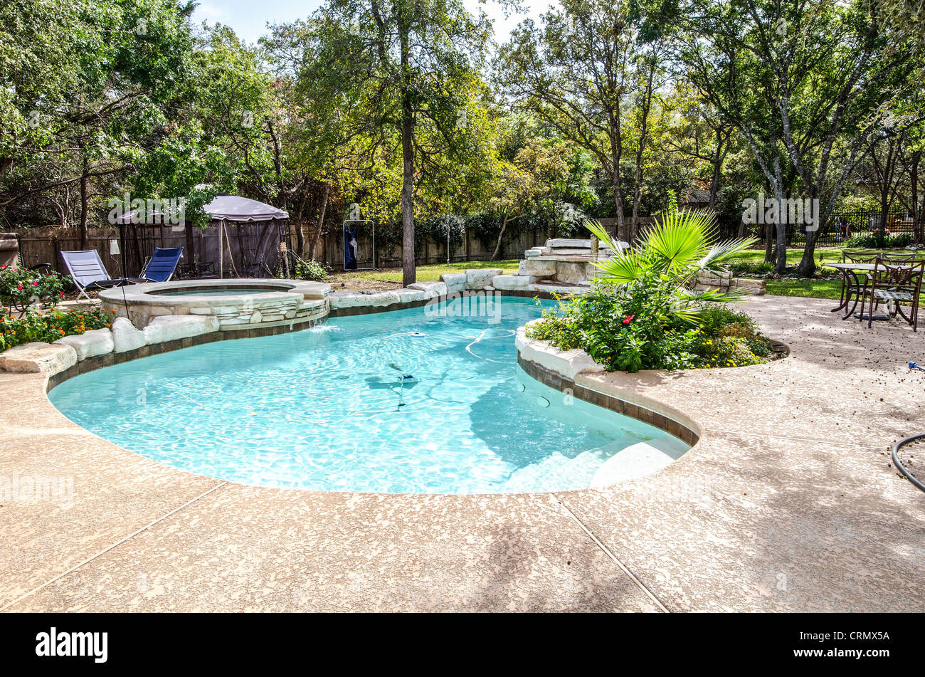 kidney shaped swimming pool and tub in landscaped backyard