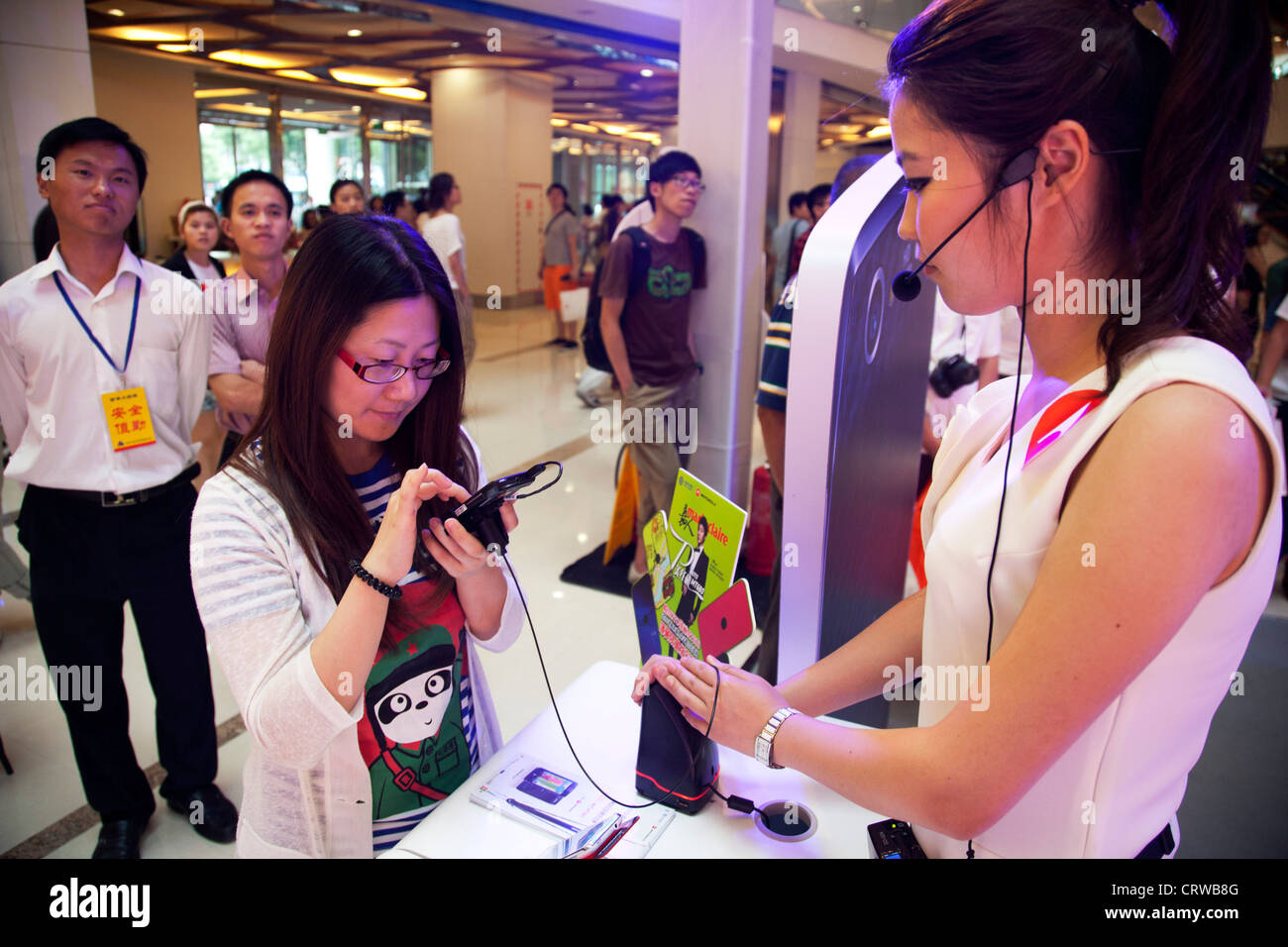 s assistant explains mobile deals to a customer pr by cell s assistant explains mobile deals to a customer pr by cell phone company mororola at joy city shopping mall beijing