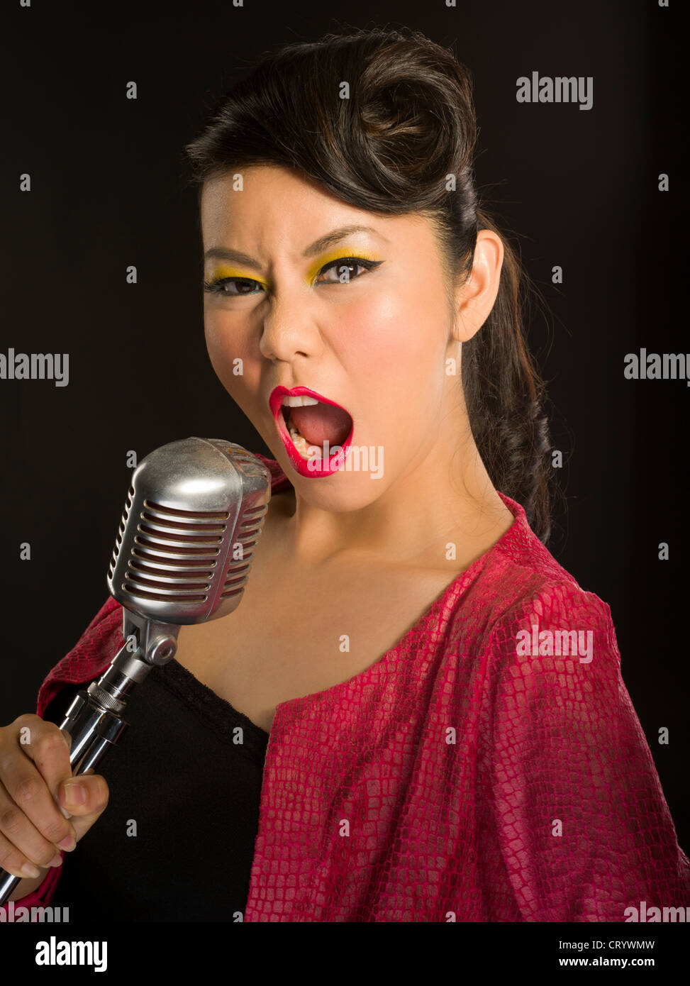 asian girl singing into a traditional elvis style shure