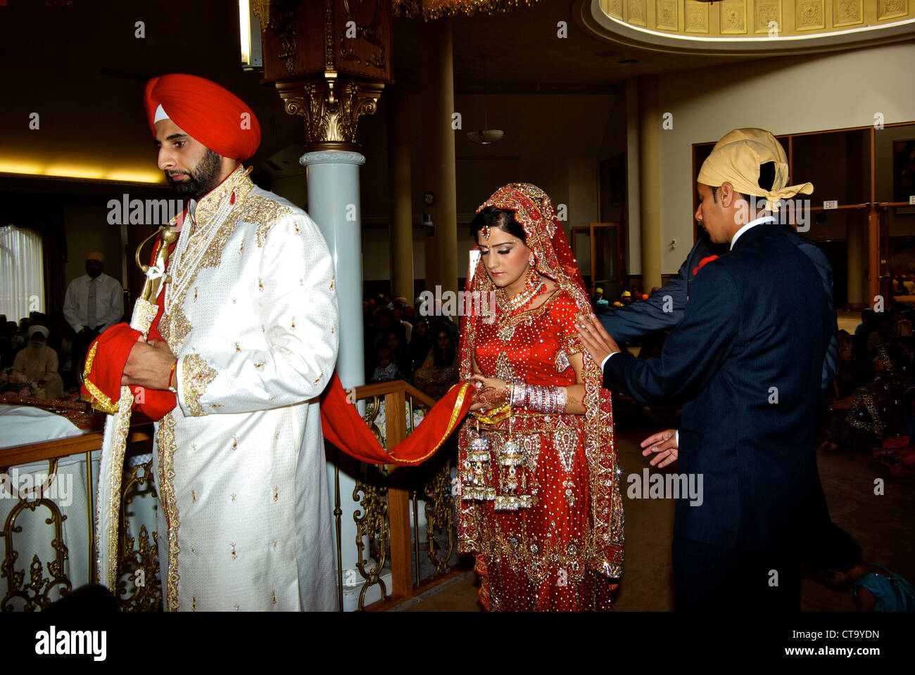 Traditional East Indian Wedding Groom Wearing Bright Red Turban Leading Bride Around Sikh Temple Altar Joined Marriage Scarf