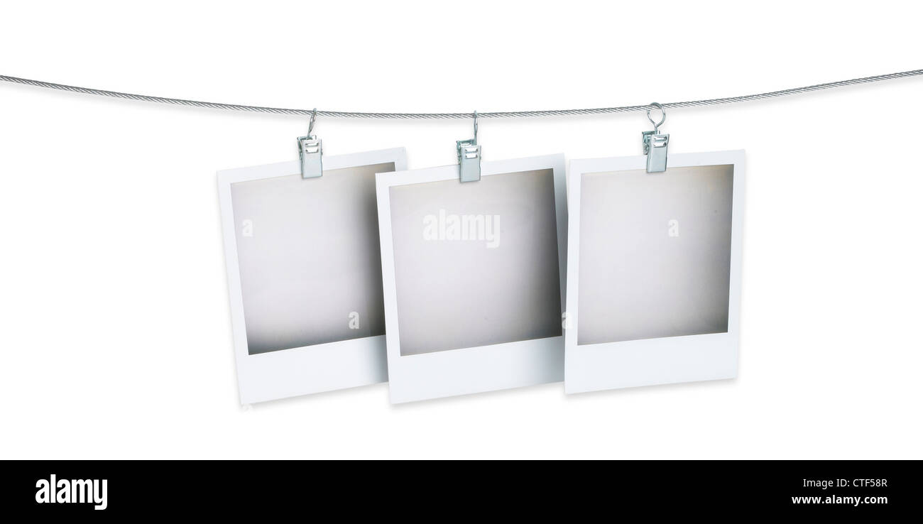 Hanging Pictures On Wire three blank polaroid pictures hanging on a wire isolated on white