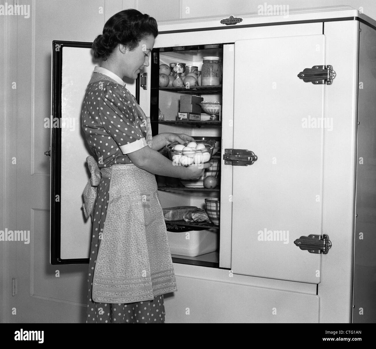 1930s housewife in apron taking eggs out of bowl from icebox   stock image appliances 1930s stock photos  u0026 appliances 1930s stock images   alamy  rh   alamy com
