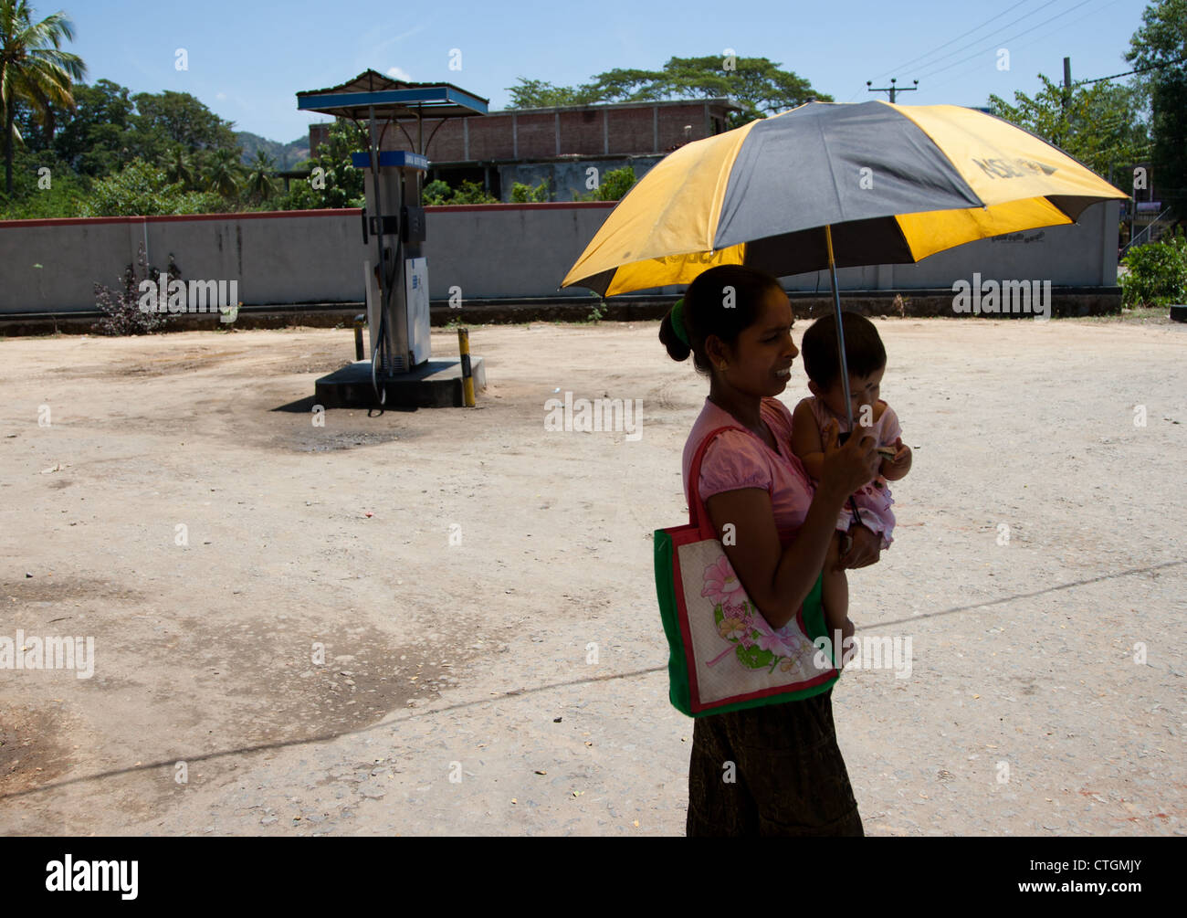 woman and child with umbrella in sri lanka stock photo royalty