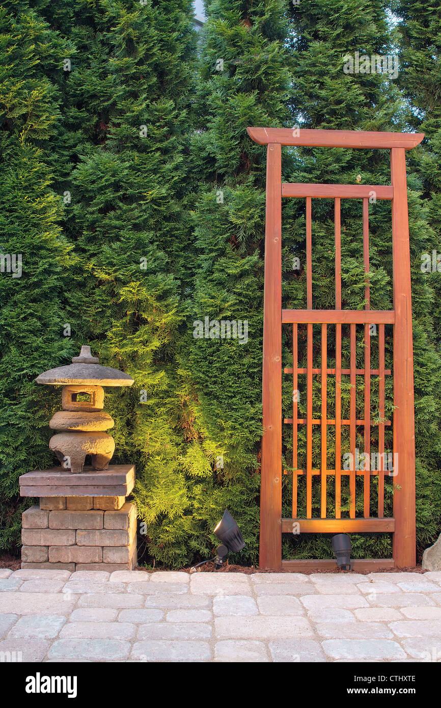 japanese stone pagoda lantern and trellis in backyard paver patio