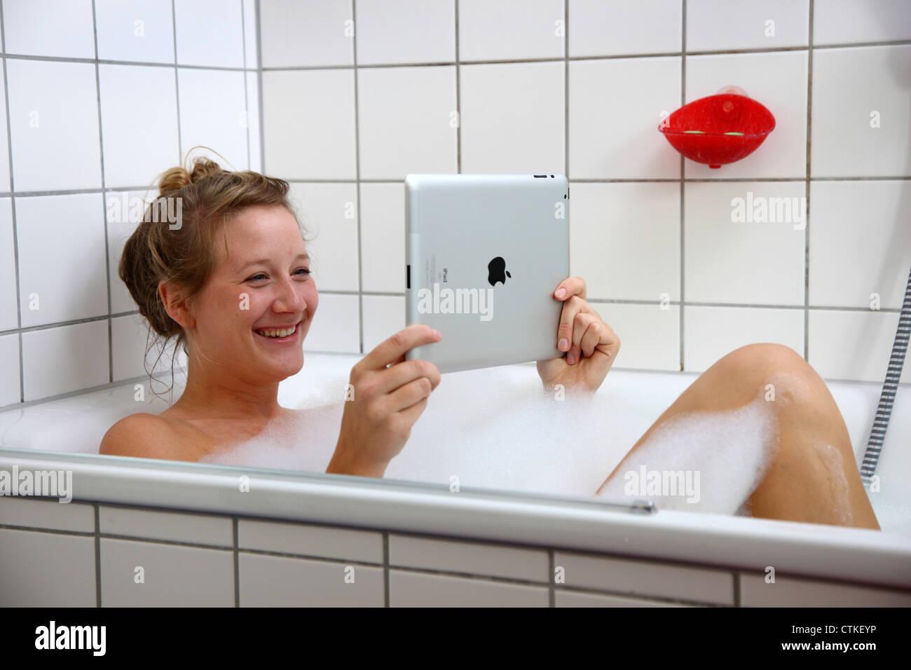 Young woman is lying in a bathtub taking a bath reading for Tablett badewanne