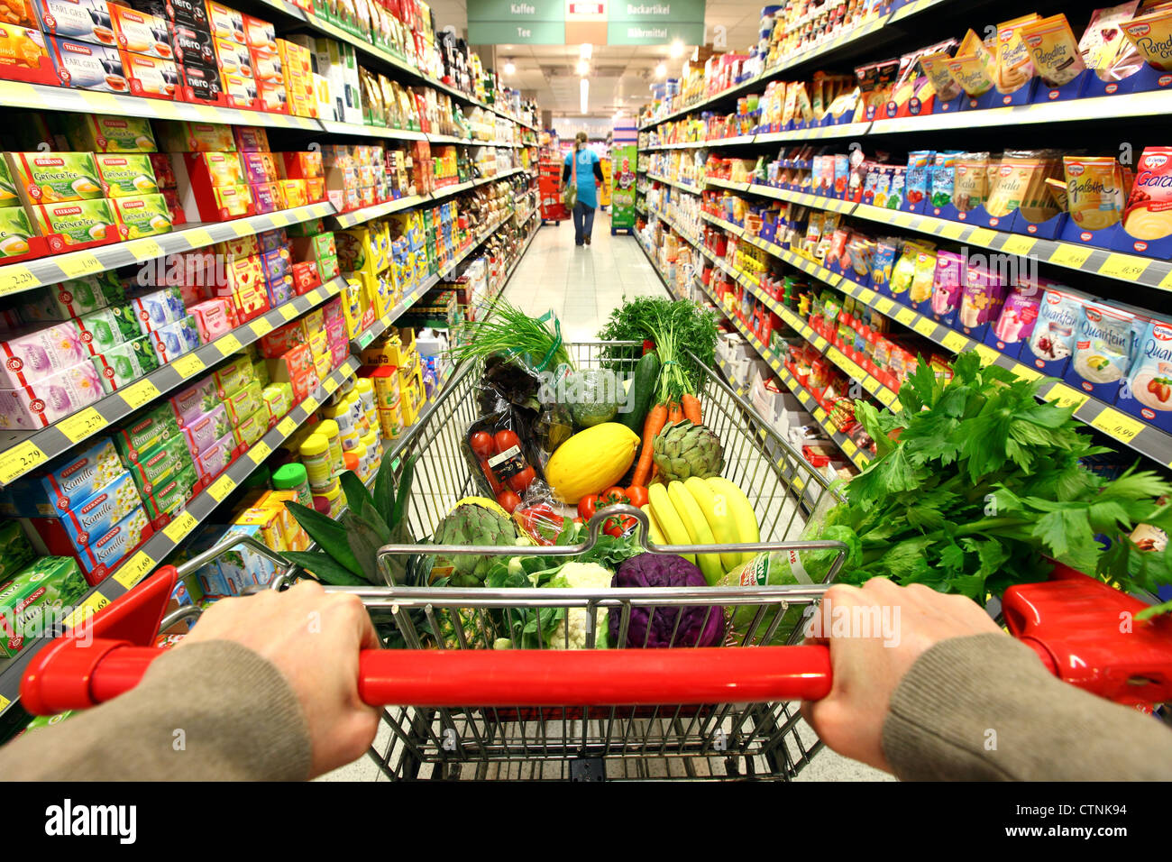 Food hall full shopping trolley is pushed through a for Shopping cuisine