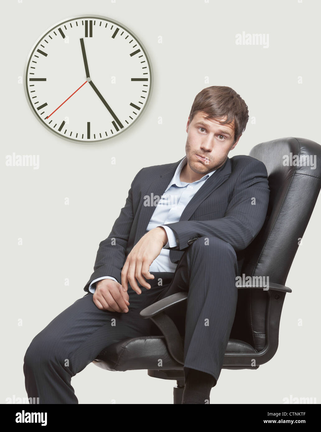 Frustrated office worker on the phone holding stock photo image - Frustrated Young Business Man Waiting For The End Of The Workday