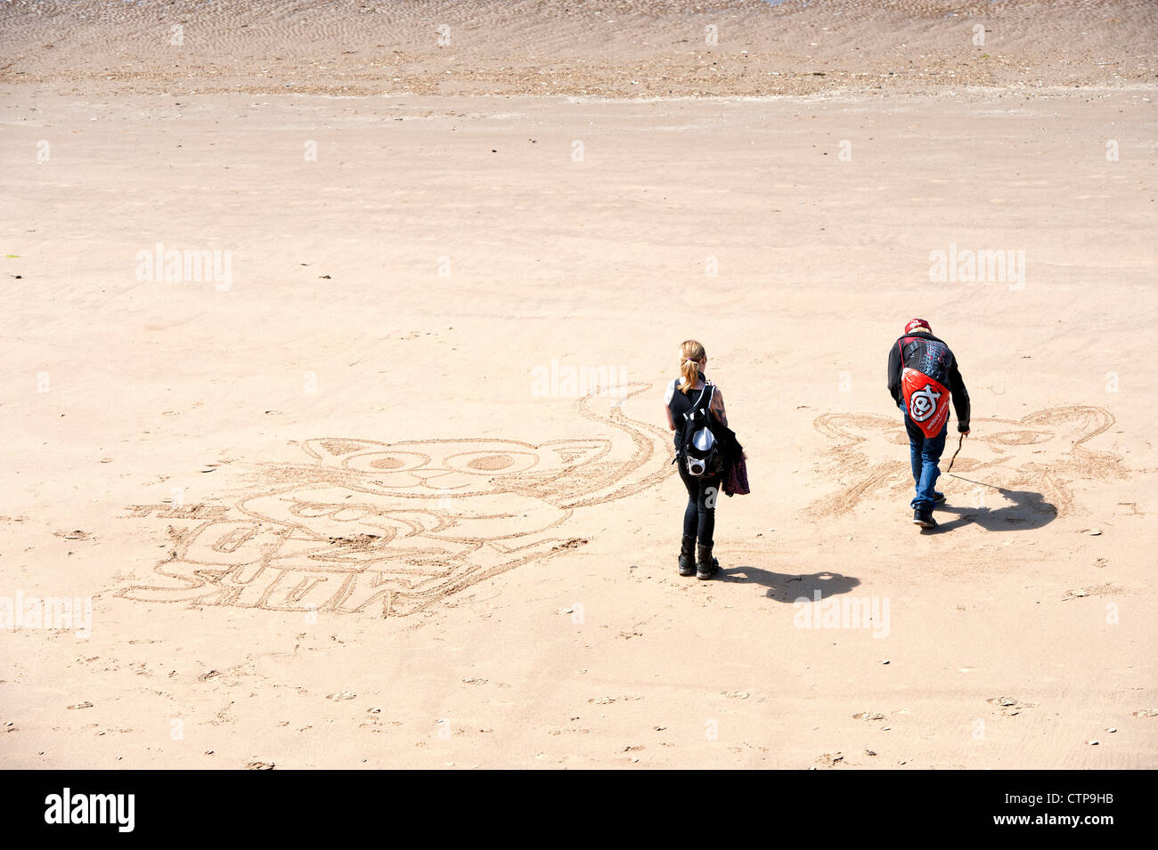 Two People Drawing Cartoon Characters On A Beach In Blackpool Lancashire