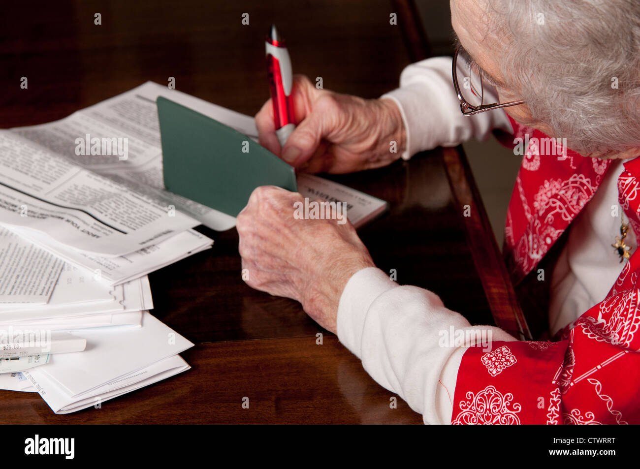 Elderly Woman Writing A Check And Paying Personal Finance Bills