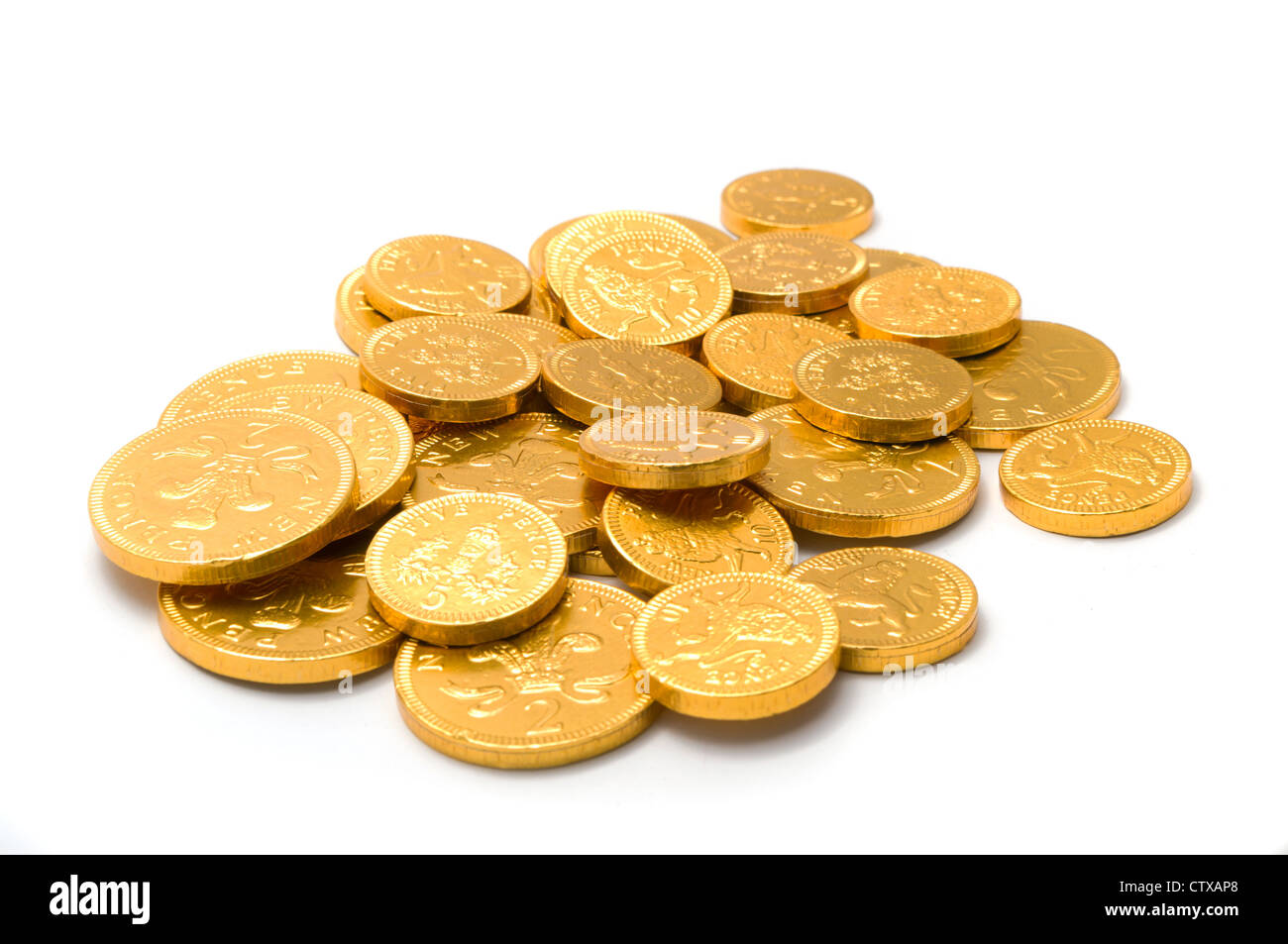 Gold-wrapped chocolate coins piled on a white background Stock ...