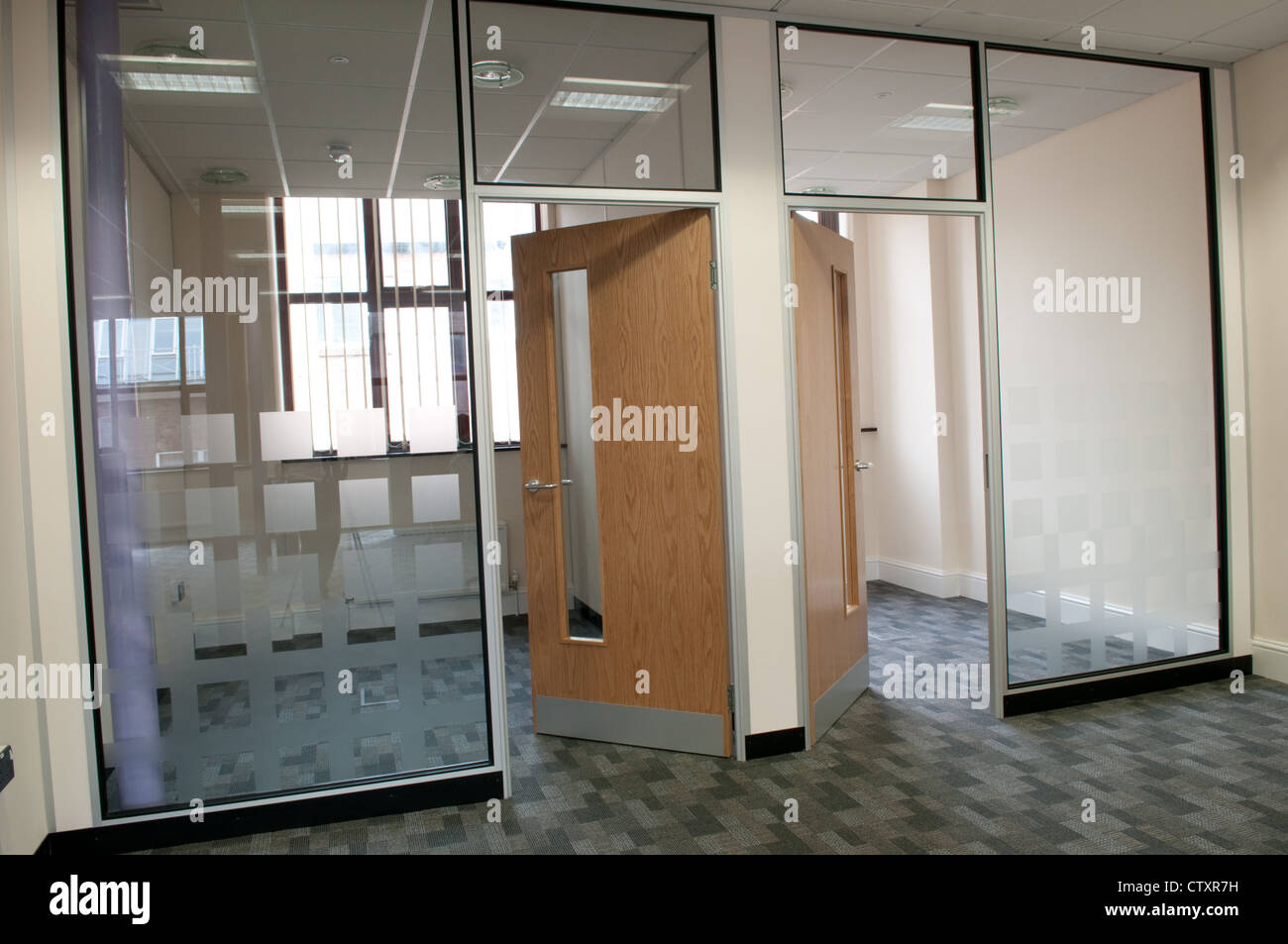 Open Doors Leading To Two Empty Offices Behind Frosted