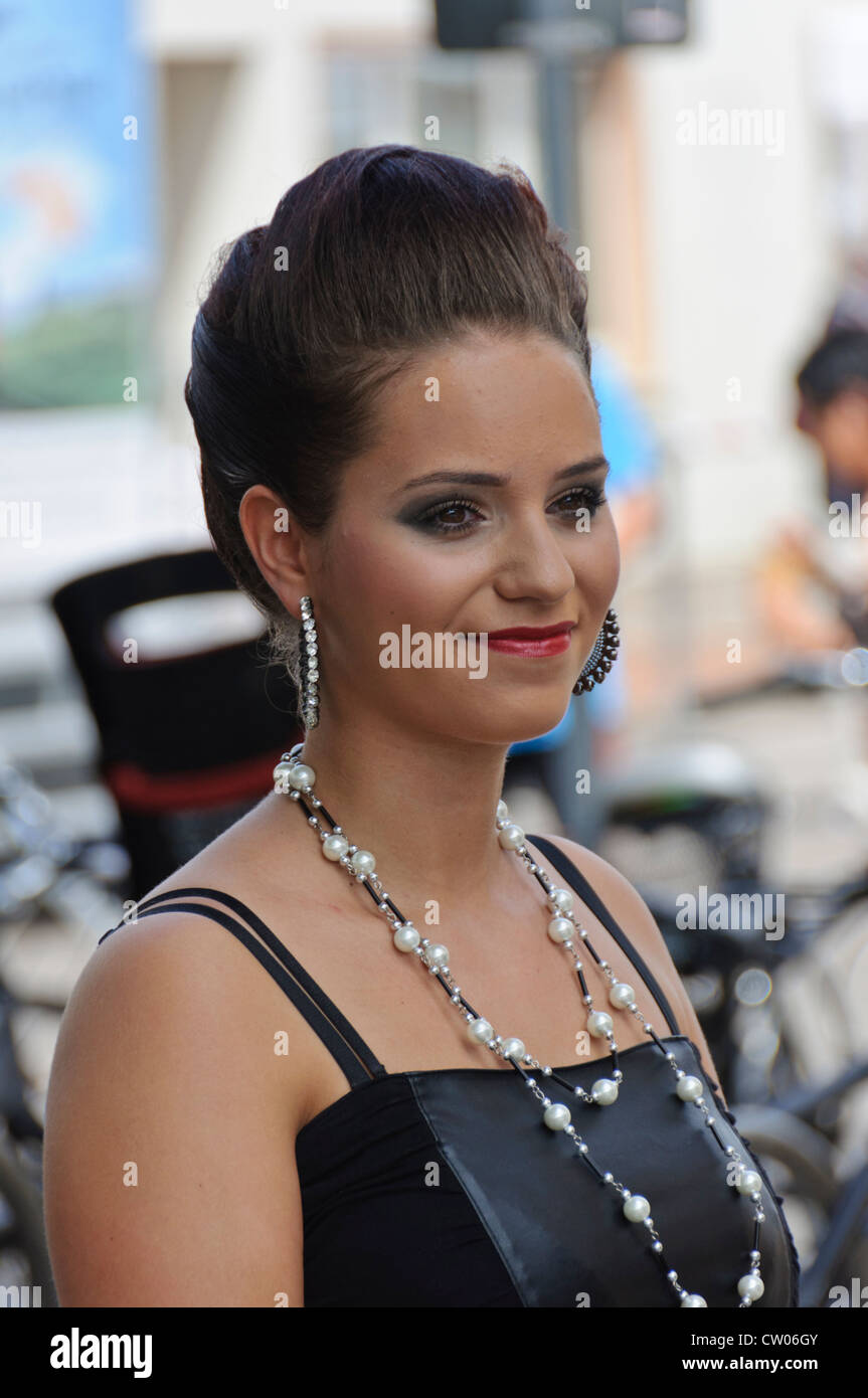 Black dress hairstyle - Stock Photo Tanned Model With Pinned Up Hairstyle In Little Black Dress Pearl Necklace Eye Catching Makeup And Big Earrings Heilbronn