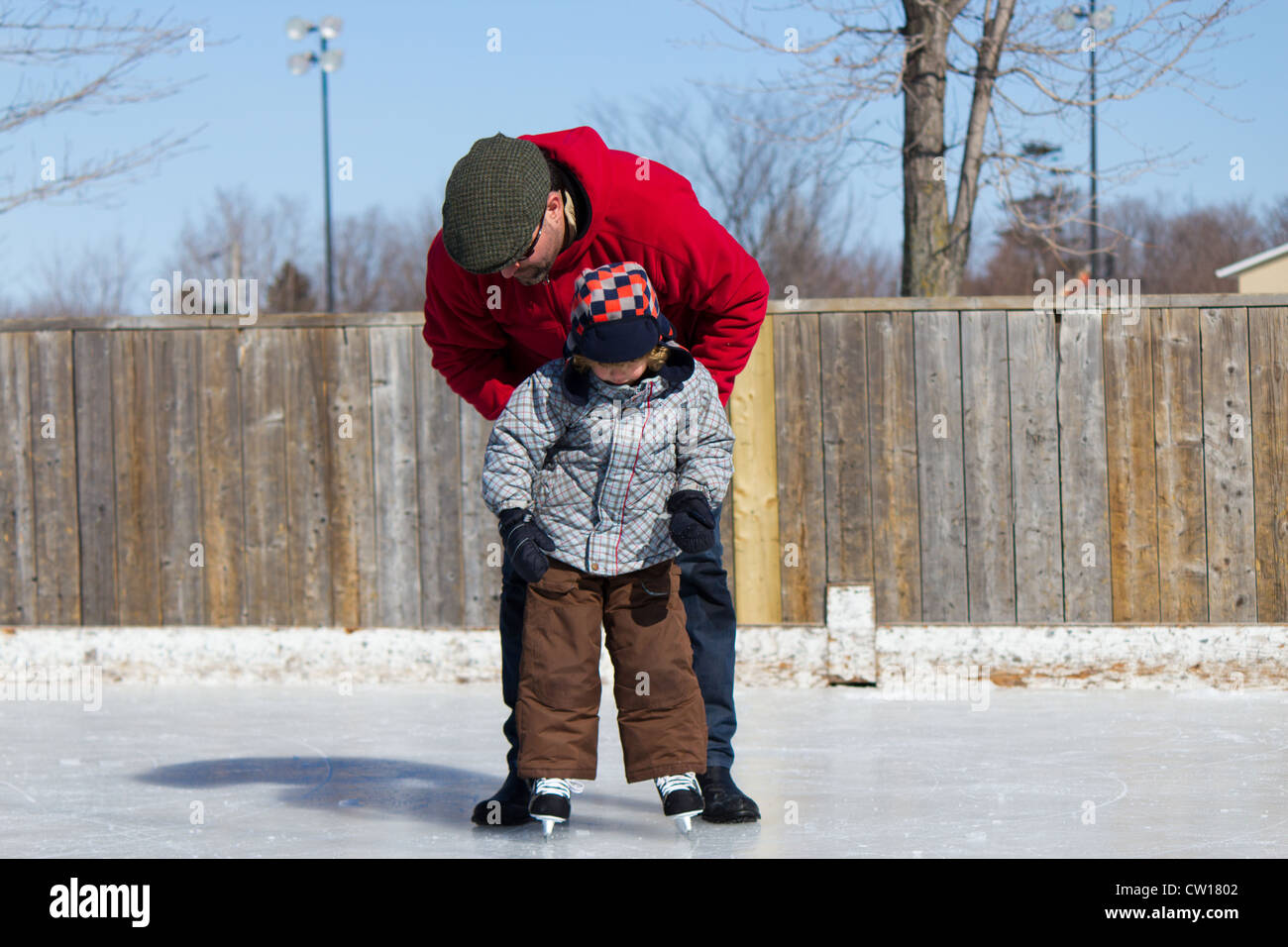 Father Teaching Son How To Ice Skate At An Outdoor Skating Rink In Winter