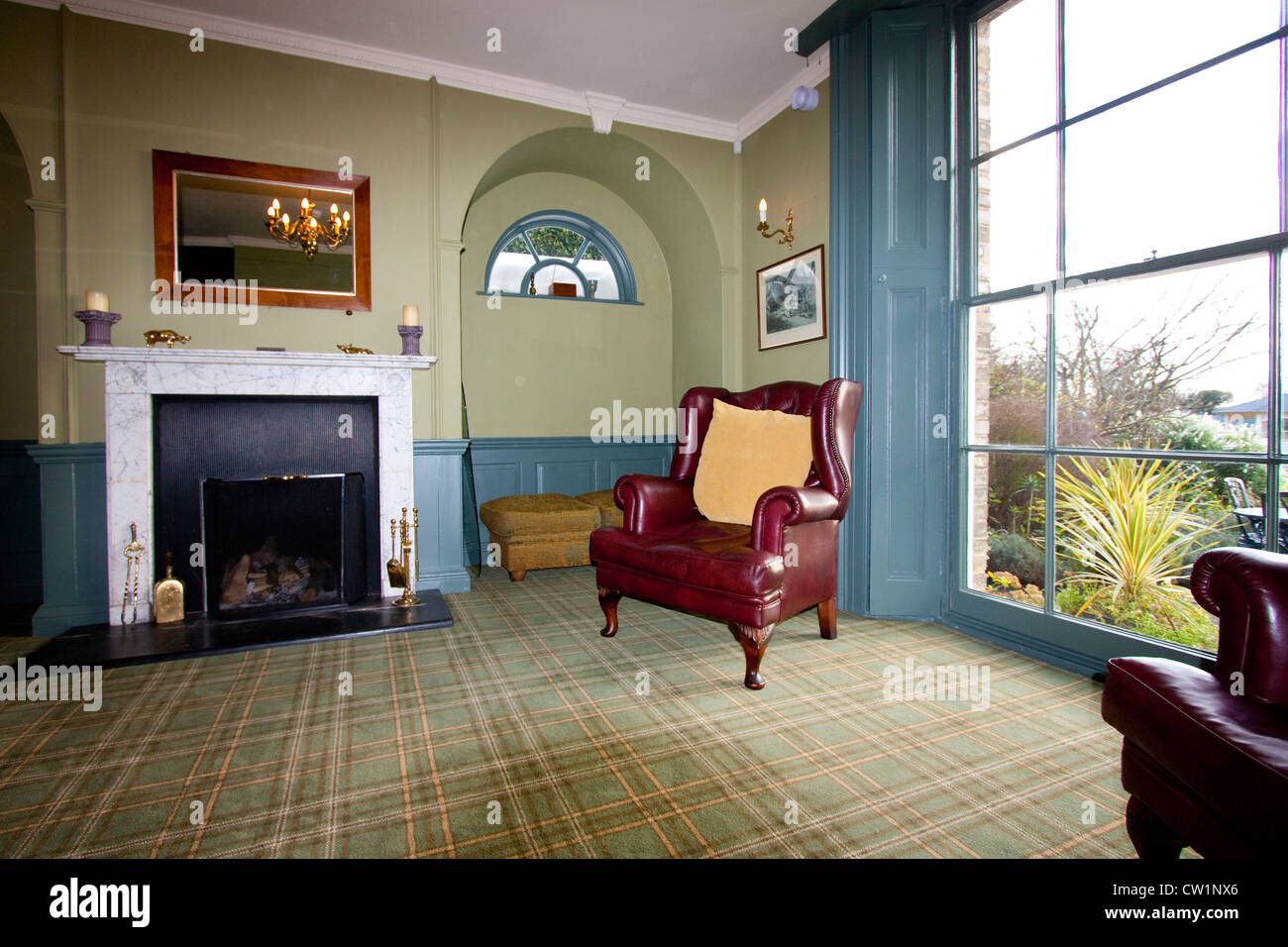 georgian style living room with fireplace and old leather armchair