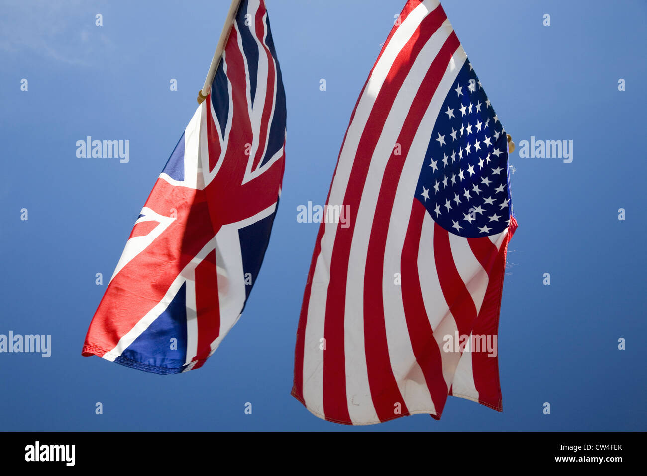 american flag hanging with union jack british flag next to white