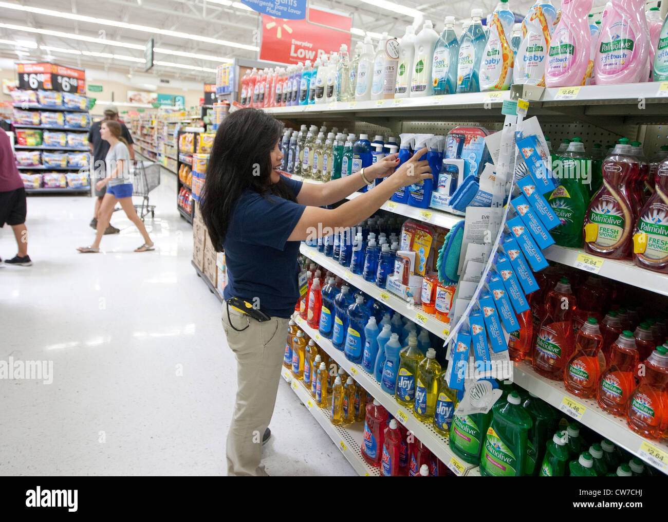 Hispanic female employee organizes cleaning products on shelves in ...