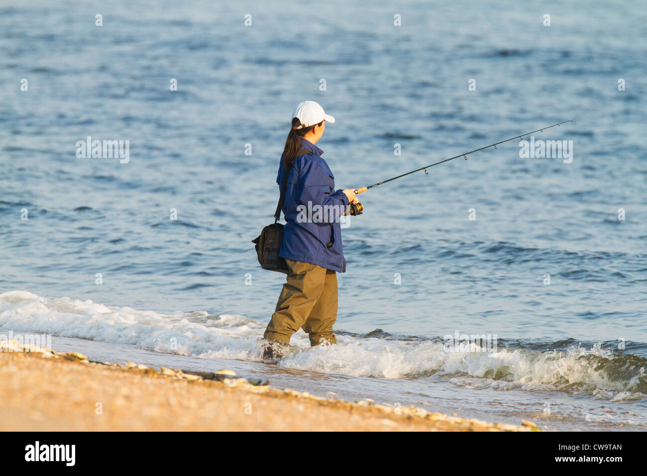 Woman wearing waders fishing in the atlantic ocean stock for Surf fishing waders