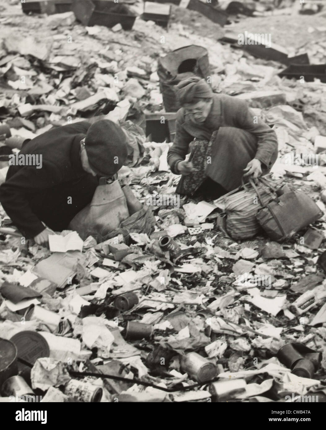World war ii two germans searching for food in a garbage for Germany rebuilding after ww2