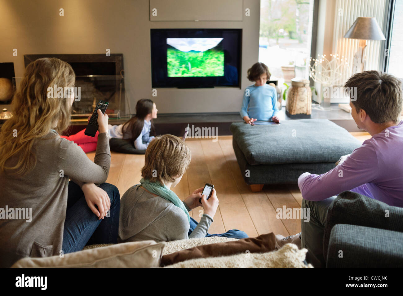 Family using electronic gadgets in a living room stock for Modern living room gadgets